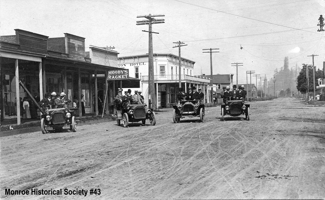 0043 – Men in their Sunday best in four early automobiles on East Main Street c1907