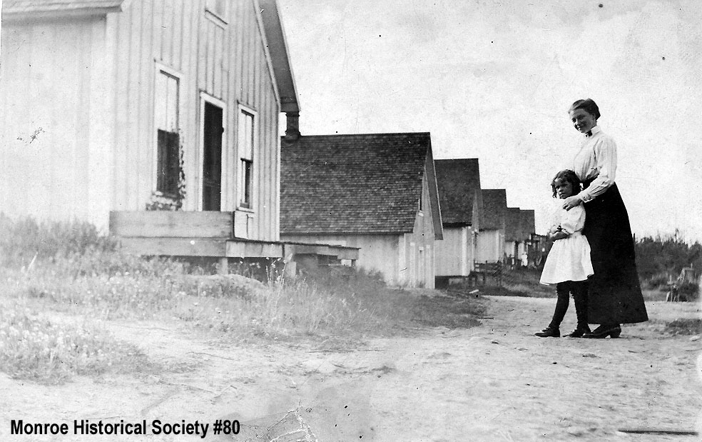 0080 – Main Street of the Three Lakes Mill Camp with the Mitchells, mother and daughter