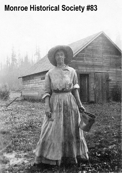 0083 – Mrs. Phebe Petticord about 1905 in front of a barn in the Woods Creek Valley
