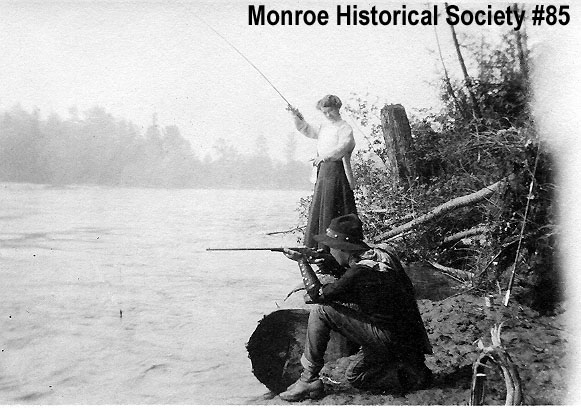 0085 – Woman fishing and man aiming rifle along the banks of the Skykomish River
